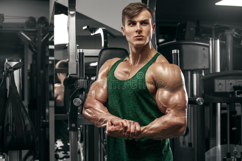 Muscular man showing muscles working out in gym, strong male with big biceps royalty free stock photography