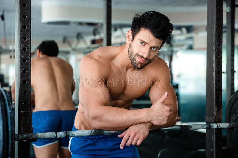 Muscular man showing thumb up in fitness gym stock photo