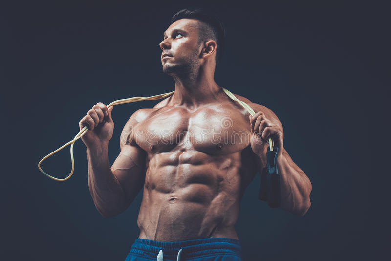 Muscular man skipping rope. active sport fitness. Muscular man skipping rope. Portrait of muscular young man exercising with jumping rope on black background stock image
