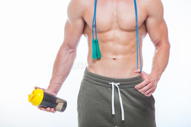 Muscular man skipping rope. Portrait of muscular young man with jumping rope drinking water with over neck, isolated on royalty free stock images