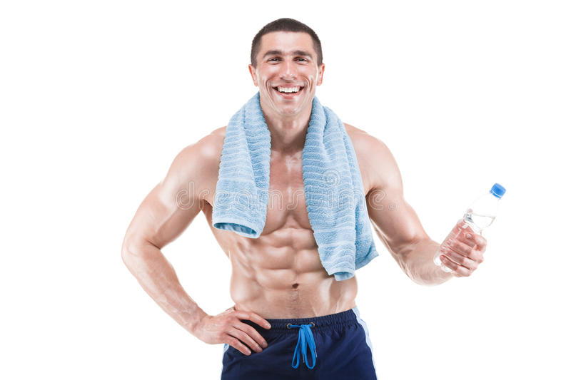 Muscular man smiling with blue towel over neck, drinking water, isolated on white background royalty free stock photography