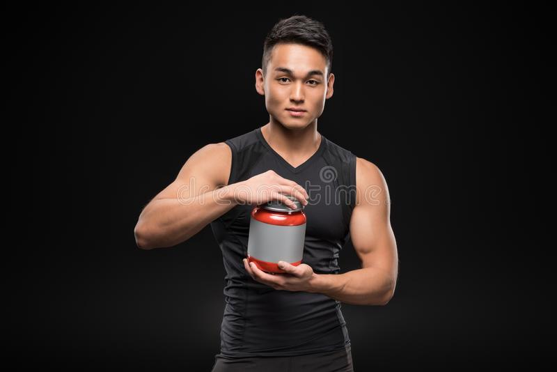 young muscular asian sportsman opening container with sport nutrition stock photo