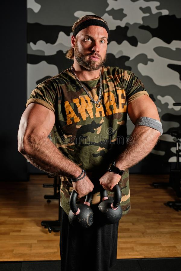 A muscular man in a sports shirt with a military print stands with kettlebells in his hands in the gym. Vertical shot stock photography