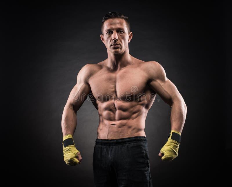 Muscular man in studio on dark background stock image