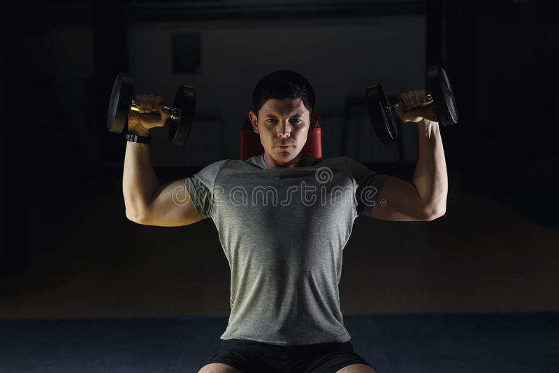 Muscular man training his shoulders with dumbbells. Muscular man training his shoulders with dumbbells stock photo