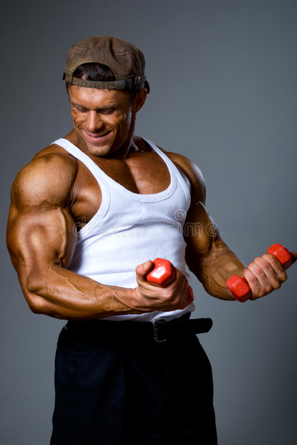 Muscular man training with small dumbbells. Comic training royalty free stock photo