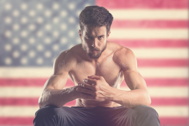 Muscular man with US flag behind. Muscular man royalty free stock photo