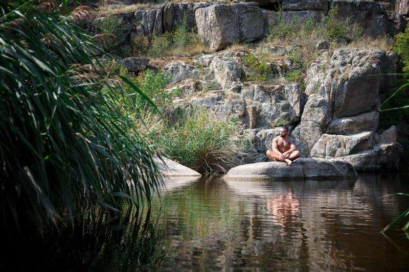 A strong young man sits on a rock in the middle of the water in summer. Summer swimming in the river among rocks. royalty free stock photos