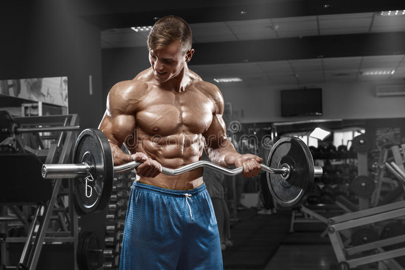 Muscular man showing muscles, posing in gym. Strong male