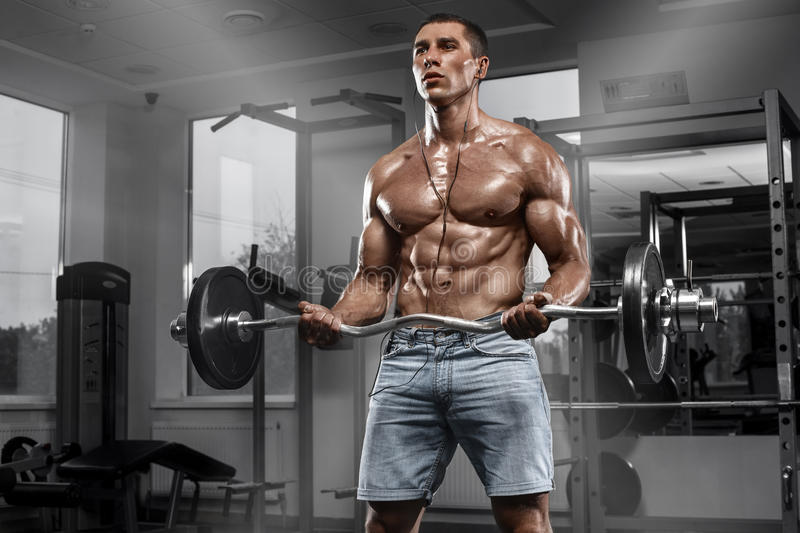 Muscular man working out in gym doing exercises with barbell, strong male naked torso abs stock photo