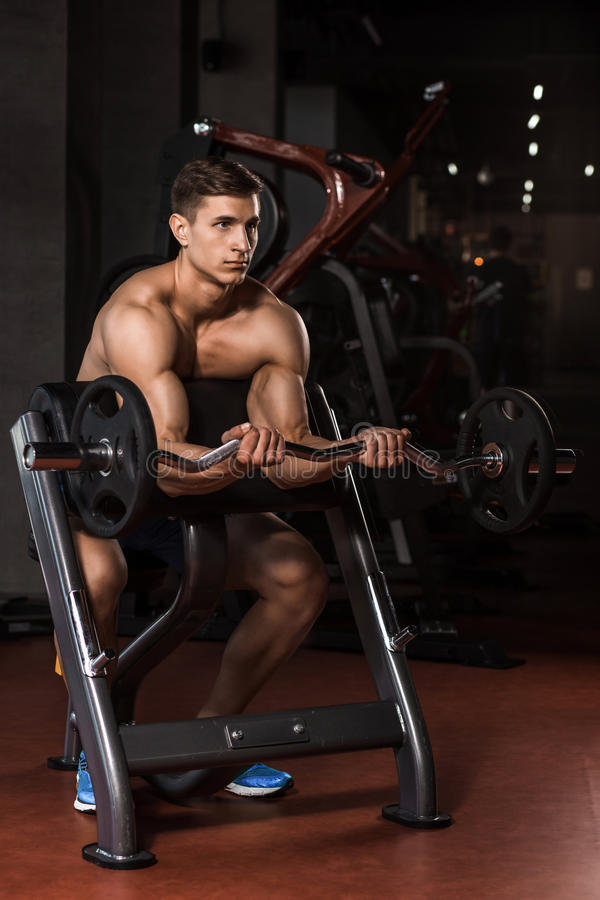 Muscular man working out in gym doing exercises with barbell royalty free stock photo