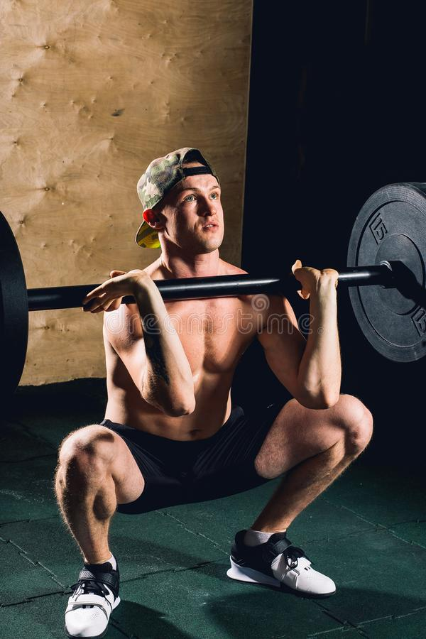 Man lifting weights. muscular man workout in gym doing exercises with barbell royalty free stock photos