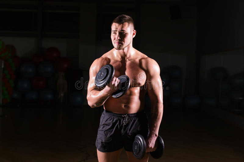 Muscular man working out in gym doing exercises with dumbbells at biceps, strong male naked torso abs. stock photography