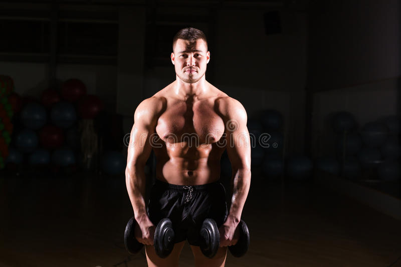 Muscular man working out in gym doing exercises with dumbbells at biceps, strong male naked torso abs. royalty free stock images