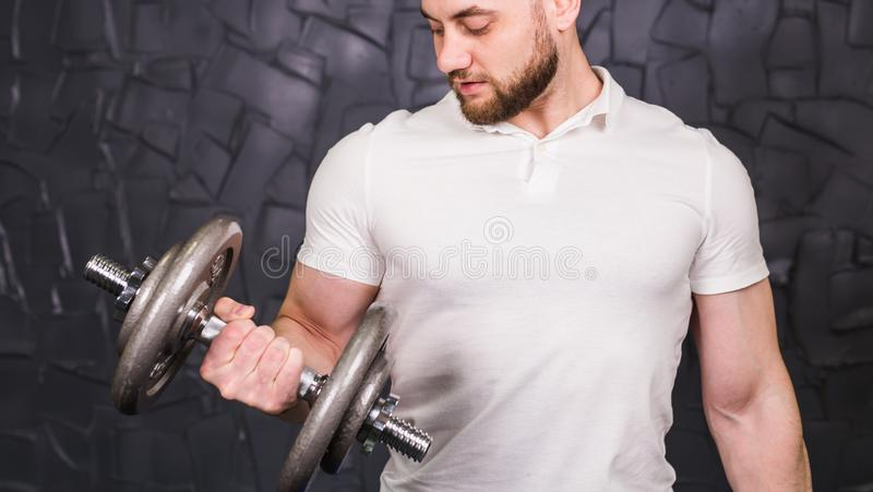 Muscular man working out in gym doing exercises with dumbbells at biceps, strong male naked torso abs. stock image