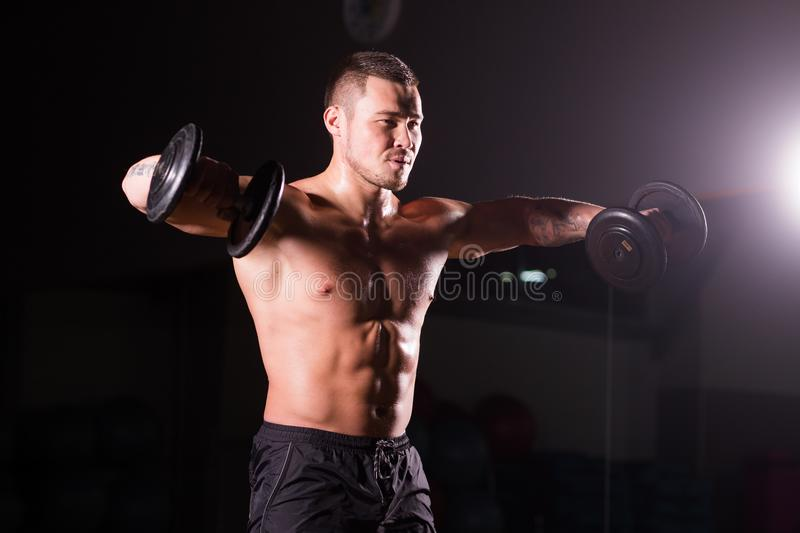 Muscular man working out in gym doing exercises with dumbbells at biceps, strong male naked torso abs. stock photo
