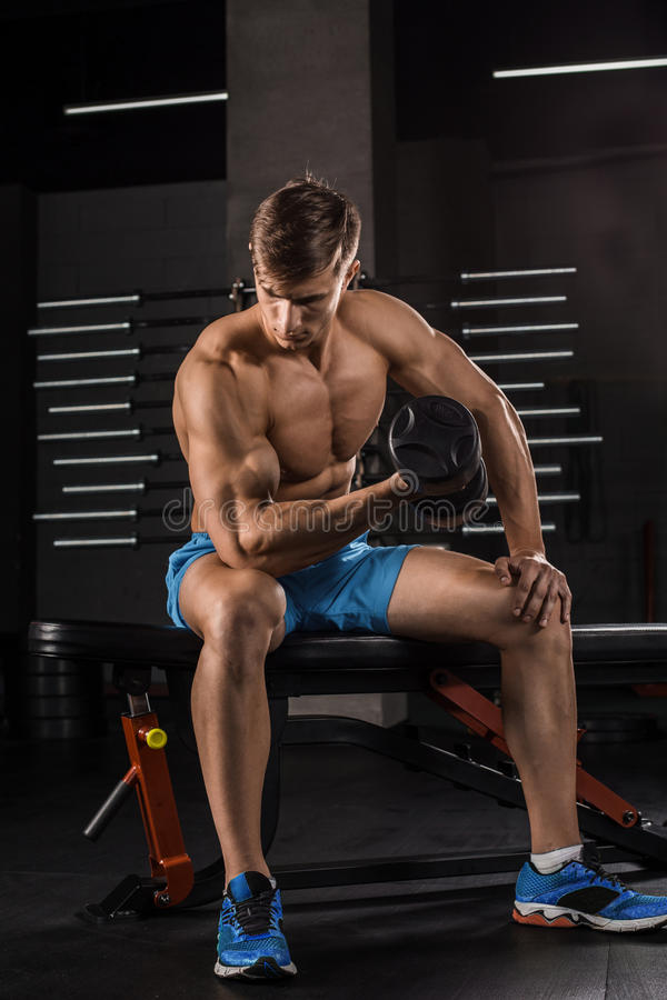 Muscular man working out in gym doing exercises with dumbbells stock photography