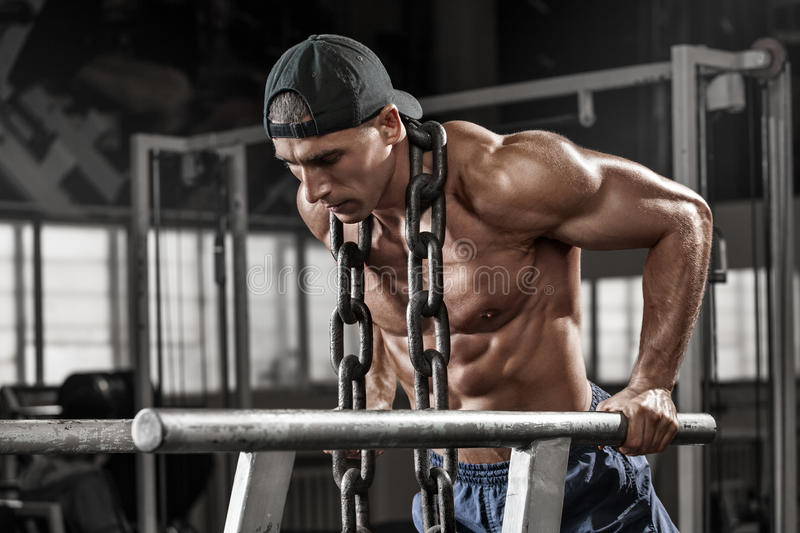 Muscular man working out in gym doing exercises on parallel bars with chain, strong male naked torso abs stock image