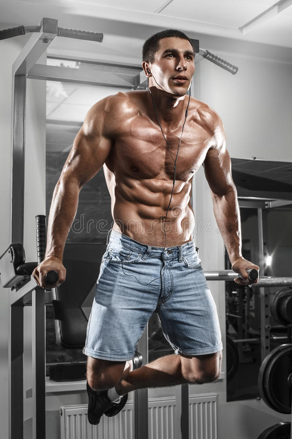 Muscular man working out in gym doing exercises on parallel bars, strong male naked torso abs stock image