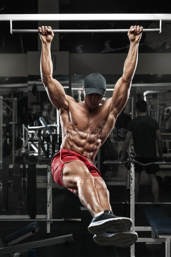 Muscular man working out in gym, doing stomach exercises on a horizontal bar, strong male naked torso abs royalty free stock photography