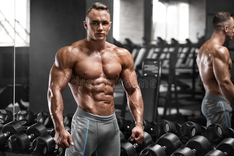 Muscular man working out in gym, strong male naked torso abs.  stock photo