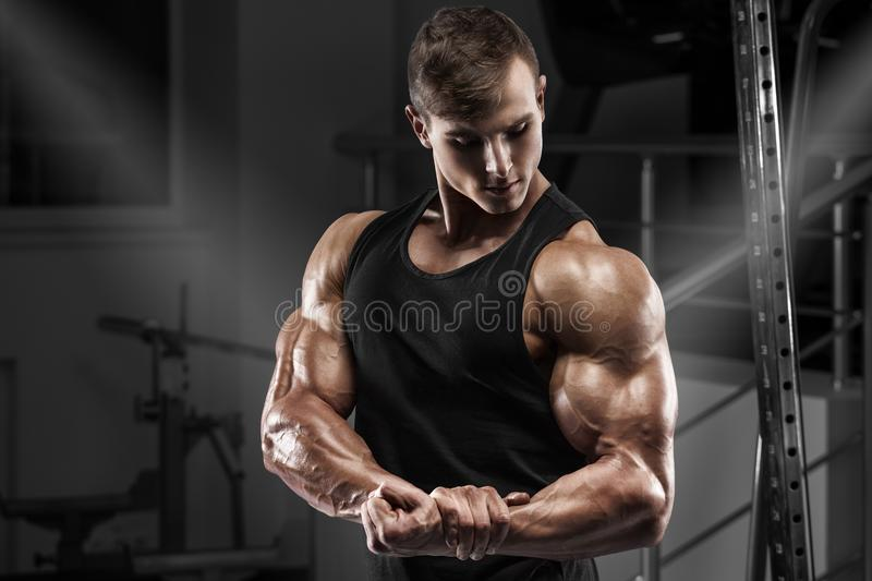 Muscular man working out in gym. Strong male showing muscles biceps.  royalty free stock images