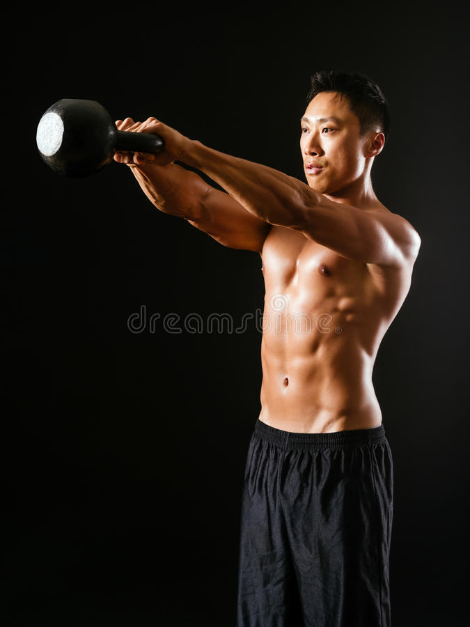 Muscular man working out with kettle bell. Photo of an Asian male exercising with a kettle bell over dark background royalty free stock images