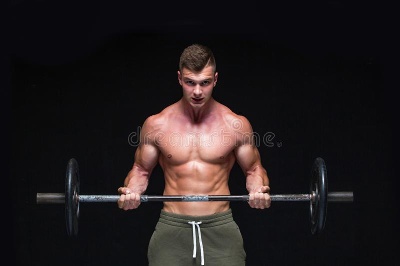 Muscular man working out in studio doing exercises with barbell at biceps, strong male naked torso abs. Isolated on. Black background. Copy Space. Strong stock photos