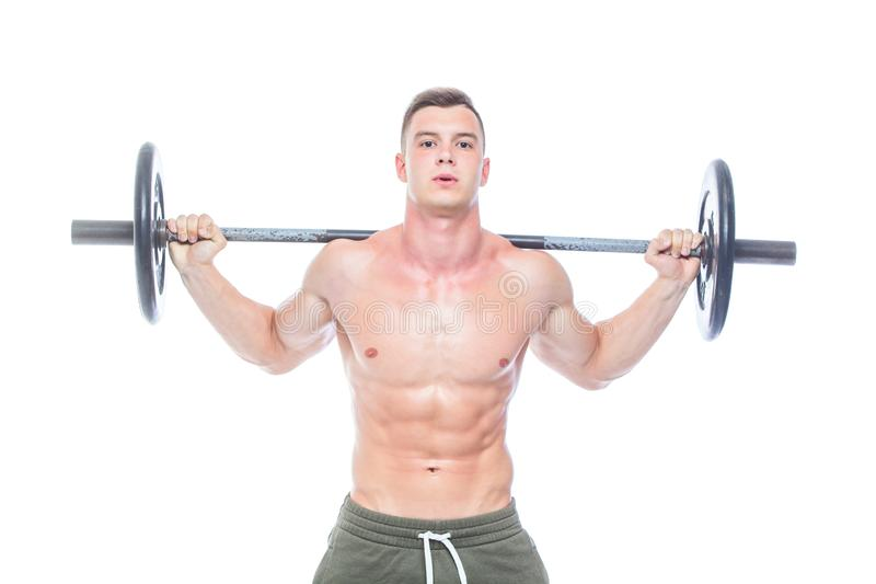 Muscular man working out in studio doing exercises with barbell at biceps, strong male naked torso abs. Isolated on. White background. Copy Space royalty free stock photo