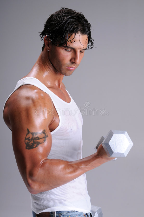 Muscular Man Workout. Muscular young man standing in jeans and a white wife beater tee shirt working out lifting weights royalty free stock images