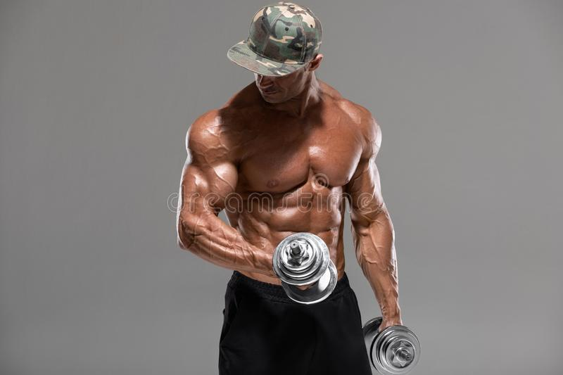 Muscular man workout doing exercises with dumbbells for biceps, isolated on the gray background. Strong male naked torso abs.  stock photography