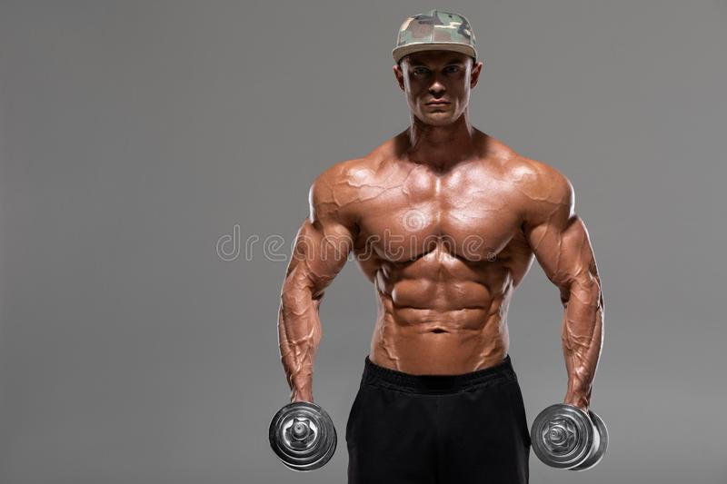 Muscular man workout doing exercises with dumbbells,  on the gray background. Strong male naked torso abs.  stock photography