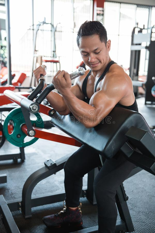 Muscular man workout on exercise machine stock photo