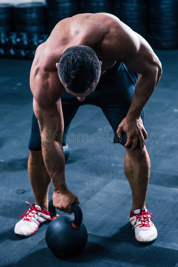 Muscular man workout with kettle ball. At gym royalty free stock photo