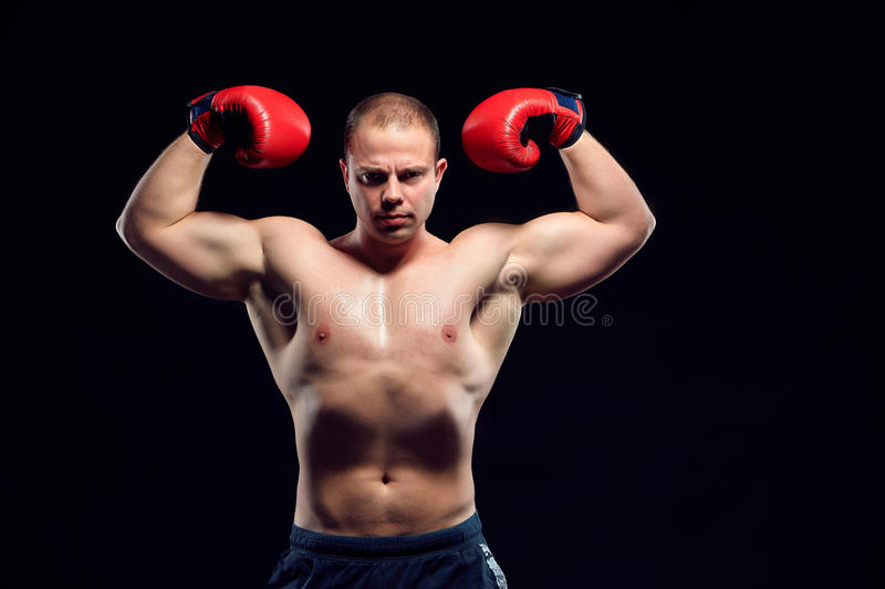 Muscular man - young caucasian boxer. In red gloves standing over black background. demonstration of strength and power royalty free stock photos