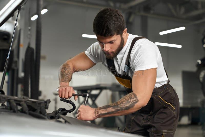 Muscular mechanic in coveralls, white t shirt repairing car. Car repair and maintenance. Young muscular mechanic in coveralls and white t shirt repairing car in stock image