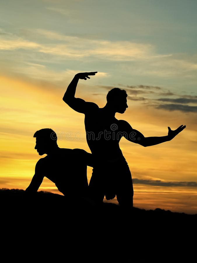 Muscular men in sunset with boxes stock images