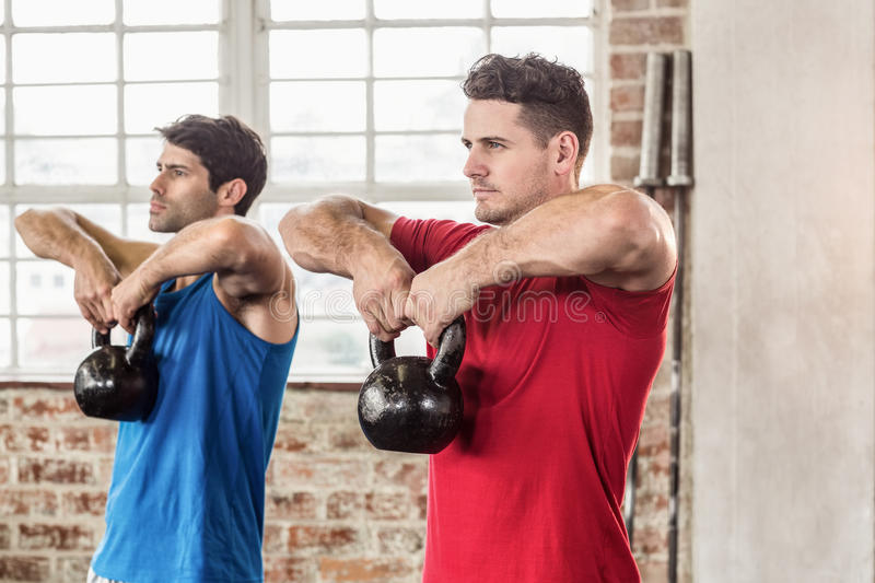 Muscular men lifting a kettle bell. In crossfit gym royalty free stock photos