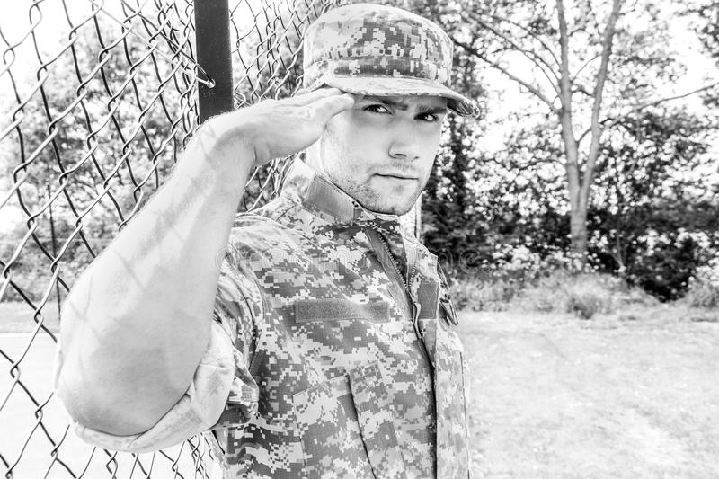 Marine, soldier in his army fatigues stands to attention and salutes at military base. Muscular military man in army fatigues and cap stands salutes camera while royalty free stock photography