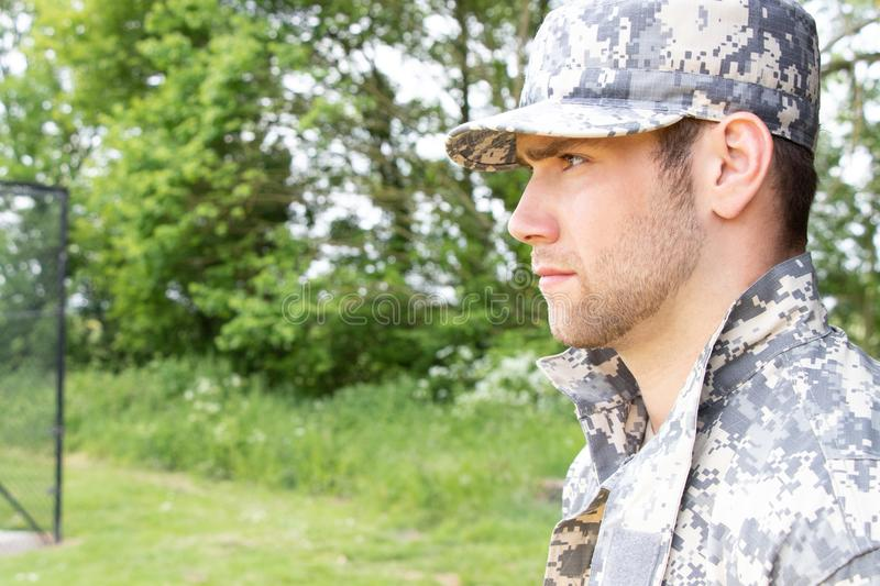 Marine, soldier in his army fatigues stands to attention at military base. Muscular military man in army fatigues and cap stands to attention while guarding army stock images