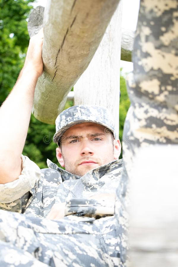 Marine, soldier in his army fatigues perform physical training on on obsticle course. Muscular military man in military fatigues at bootcamp trains on obsticle royalty free stock photography