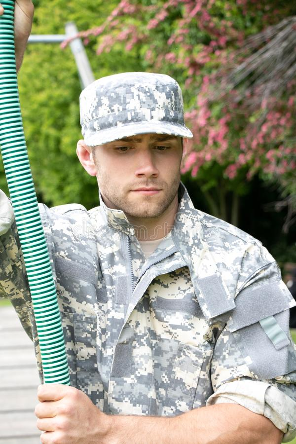 Marine, soldier in his army fatigues perform physical training on on obsticle course. Muscular military man in military fatigues at bootcamp trains on obsticle stock photos
