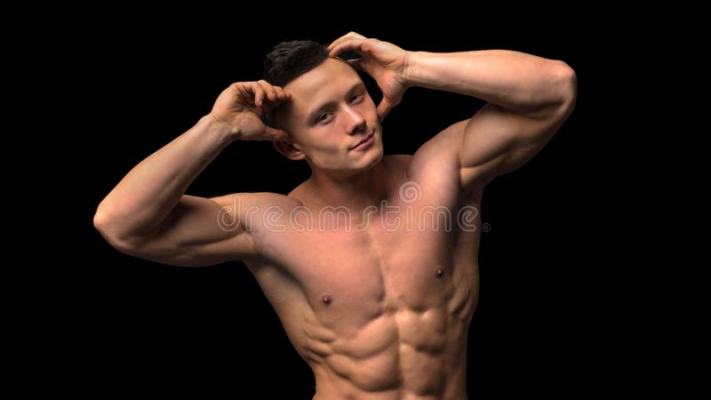 Muscular model young man on dark background. Fashion portrait of strong brutal guy with trendy hairstyle. naked stock images