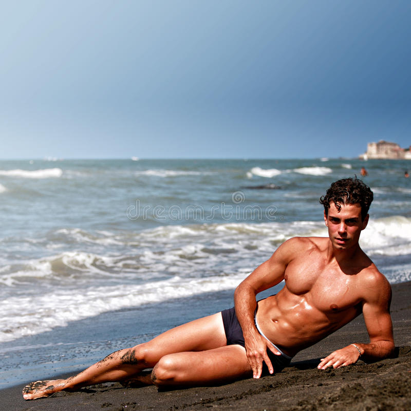 Muscular model young man lying and relaxing, sea shore stock photos