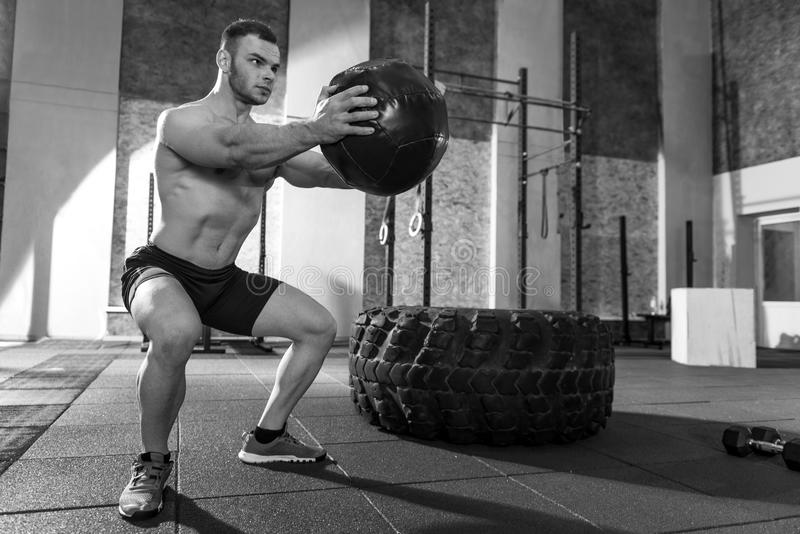 Muscular nice man exercising with a medicine ball royalty free stock photo