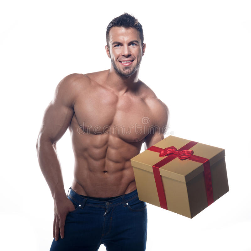 Muscular man with a gift. On a white background stock images