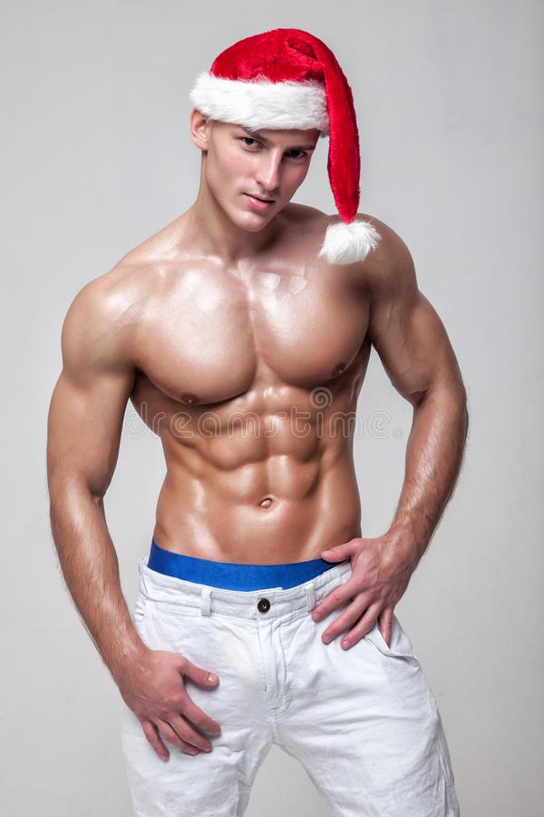 Muscular Nude guy with naked torso in Santa Claus hat posing indoors. Muscular Nude guy with naked torso in Santa hat and white shorts posing indoors royalty free stock photo