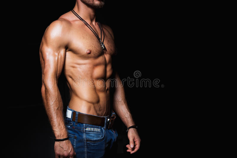 Muscular and torso of young man in jeans. Muscular and torso of young man with perfect abs royalty free stock photo