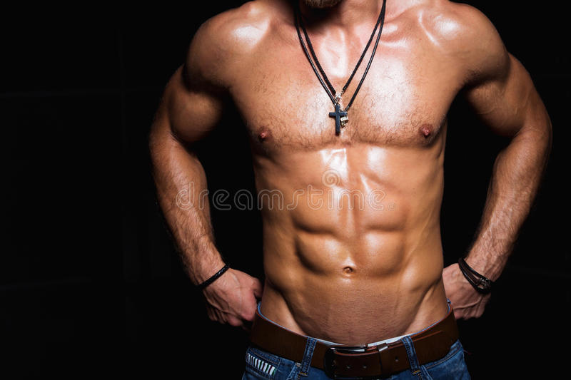 Muscular and torso of young sporty man in. Muscular and torso of young sporty man bodybuilder in jeans with perfect abs, bicep and chest royalty free stock photography