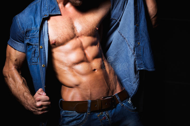 Muscular and young man in jeans shirt with. Perfect fitness body close up royalty free stock photography